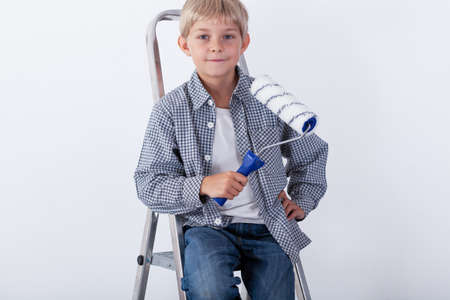 redecoration: Little boy sitting on ladder and holding paint roller Stock Photo