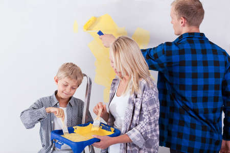 redecoration: Family painting wall on yellow in living room