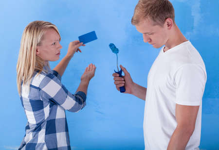 unsatisfied: Man painting wall for bad colour and unsatisfied girl Stock Photo