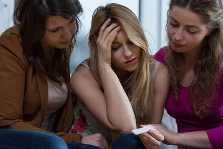 unwanted: Young pretty girl with pregnancy test and her two friends