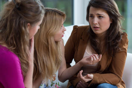 confuse: Three pretty friends having a serious conversation Stock Photo