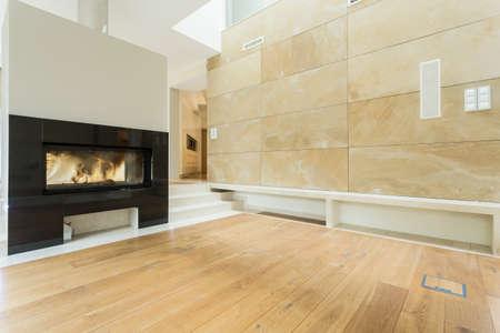 Burning fireplace in beige stylish house