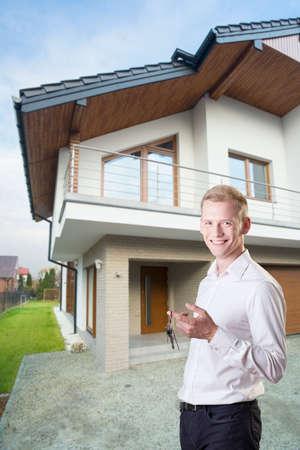 Beau jeune architecte fiers tenant les clés de sa maison