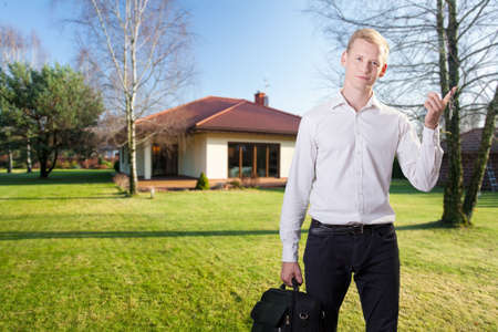 project property: Young handsome architect in front of new built house