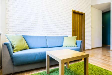 白いレンガと同じ部屋に青いソファ