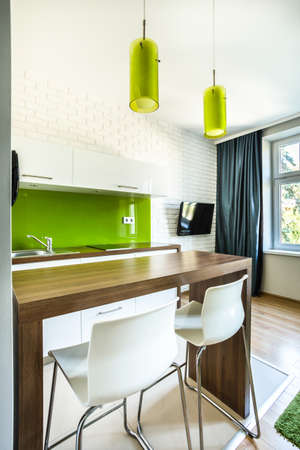small table: Green kitchenette and dining space in hotel room