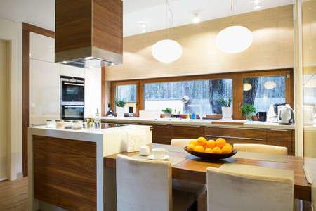muebles de madera: Cocina de madera brillante moderna con isla y mesa grande Foto de archivo