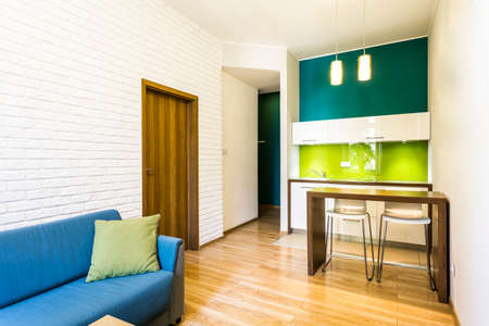 living room minimalist: Small living room with brick wall and green kitchenette