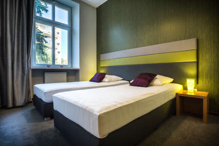 hotel suite: Two neat, single beds in green hotel room