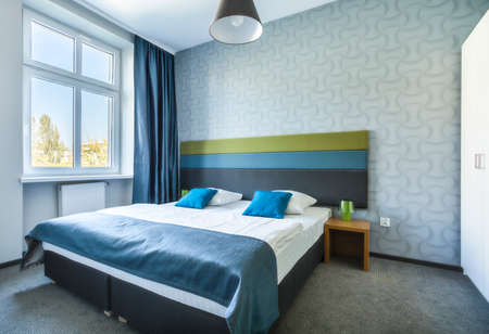 large windows: Big twin bed in modern, blue hotel apartment