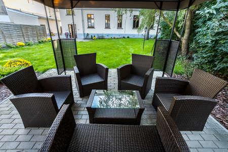 Wicker chairs on hotel's patio in garden