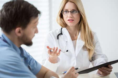 estuche: Consultoría joven pasante con otro médico Foto de archivo