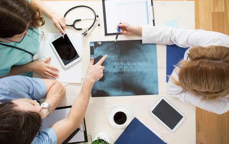 columna vertebral: Los m�dicos que se sientan alrededor de la mesa y la imagen de rayos x de interpretaci�n Foto de archivo