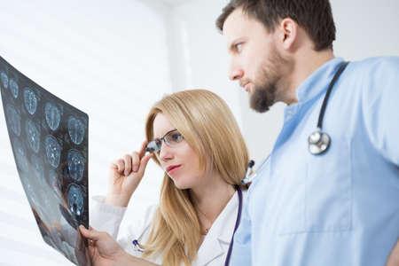 Young neurologists reading brain MRI at hospital