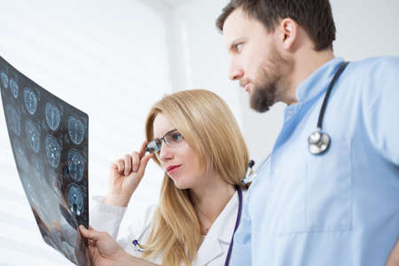 Young neurologists reading brain MRI at hospital photo