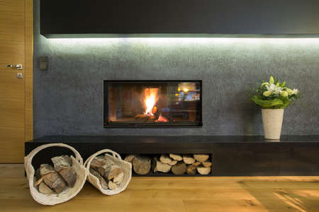 fireplace: Lighted fireplace in wall with wood stocks Stock Photo