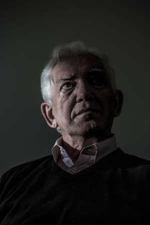 lamentable: Thoughtful sad elder man on dark background