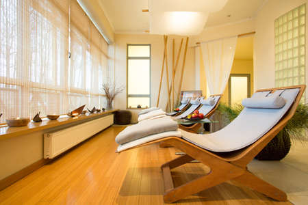 Comfortable sunbeds in relax room with wooden floor photo
