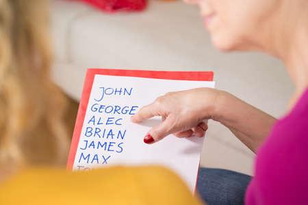 아기 이름 목록을 들고 임신 한 여자의 근접 스톡 콘텐츠