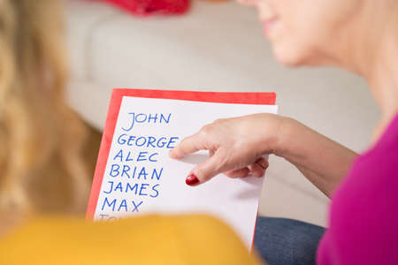 Close-up of pregnant woman holding the list of baby names Imagens