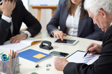 polls: Elderly businessman looking at poll results during business appointment Stock Photo