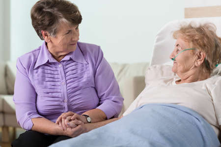 Senior woman caring about her ill sister