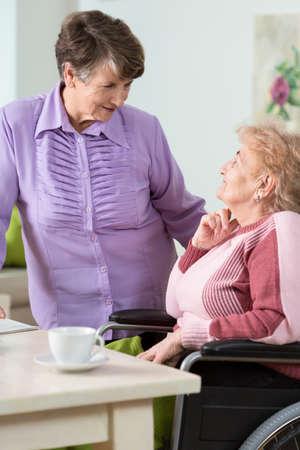 nursing sister: Senior woman using wheelchair and her sister