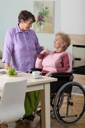 nursing sister: Caregiver helping disabled senior woman using wheelchair Stock Photo