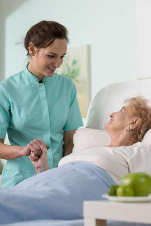 Caring nurse and ill senior woman in hospital