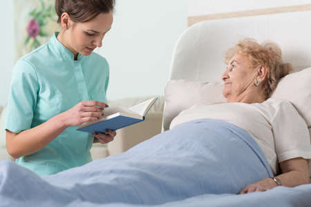 bedridden: Close-up of caregiver reading ill patient book Stock Photo