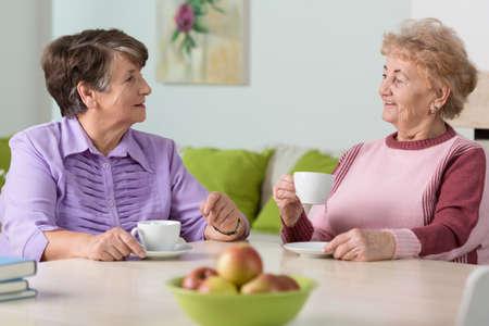 高齢女性のテーブルに座って、コーヒーを飲みながら