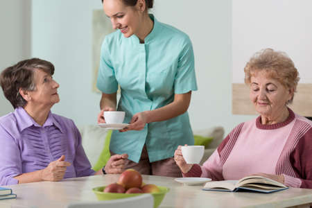 social work aged care: Caring nurse and residents of residential home