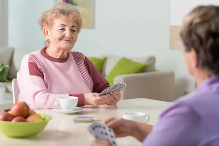 Smiling senior women playing cards at home Stock Photo