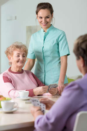 social work aged care: Female pensioners playing cards in nursing home