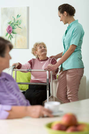 residents: Vertical view of nurse helping disabled woman Stock Photo
