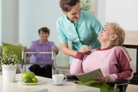 home care: Helpful nurse working in old peoples home Stock Photo