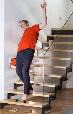 Hombre tropezando con juguete del niño en las escaleras Foto de archivo