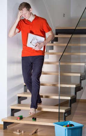 bajando escaleras: Hombre reflexivo va a tropezar en las escaleras