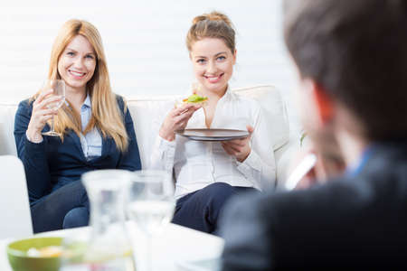 lunch meeting: Two happy businesswomen eating lunch at the office Stock Photo