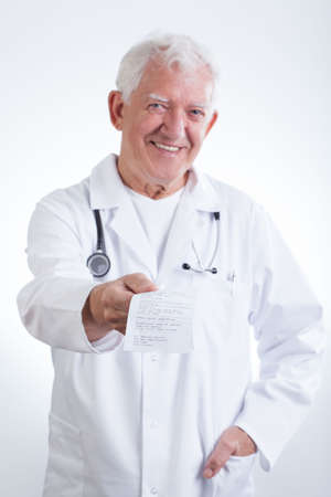 practiced: Image of smiling senior doctor giving prescription