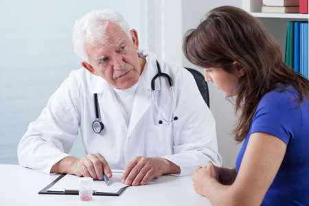 Senior doctor asking his young patient about medical history photo