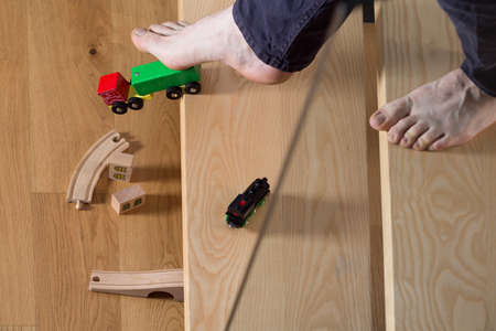 Close-up of man tripped over childs toy