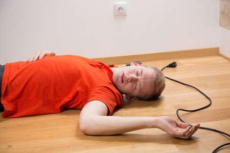 descarga electrica: Electrocutado electricista inconsciente tendido en el suelo Foto de archivo