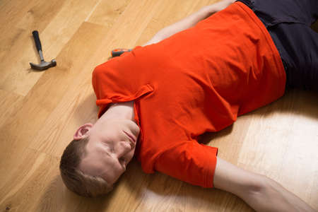 the unconscious: Image of unconscious handyman after accident during work Stock Photo