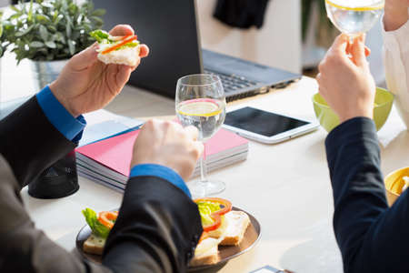 lunch meeting: Close-up of young businessman eating his sandwiches for lunch