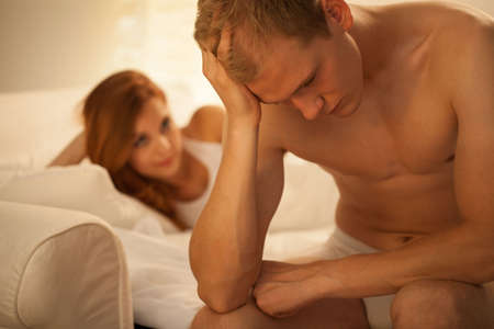 female sex: Young troubled man and his pleasant girlfriend in bed Stock Photo