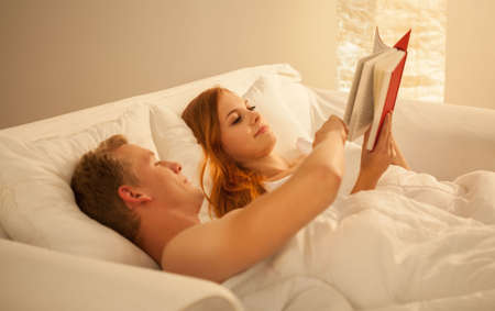 sexy couple embrace: Happy young couple reading book in bed Stock Photo