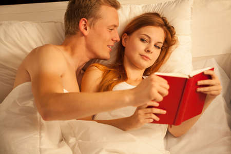 nude wife: Young handsome man persuading his wife to stop read the book