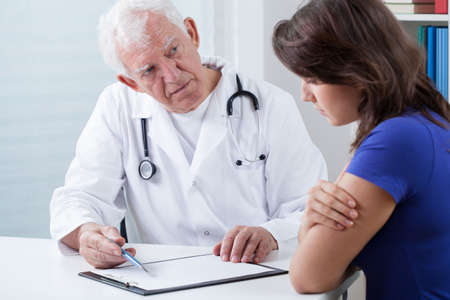 Practiced doctor doing medical interview with patient photo