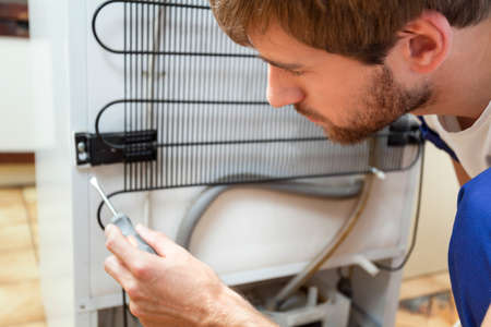 refrigerador: Hombre joven durante la reparación de nevera